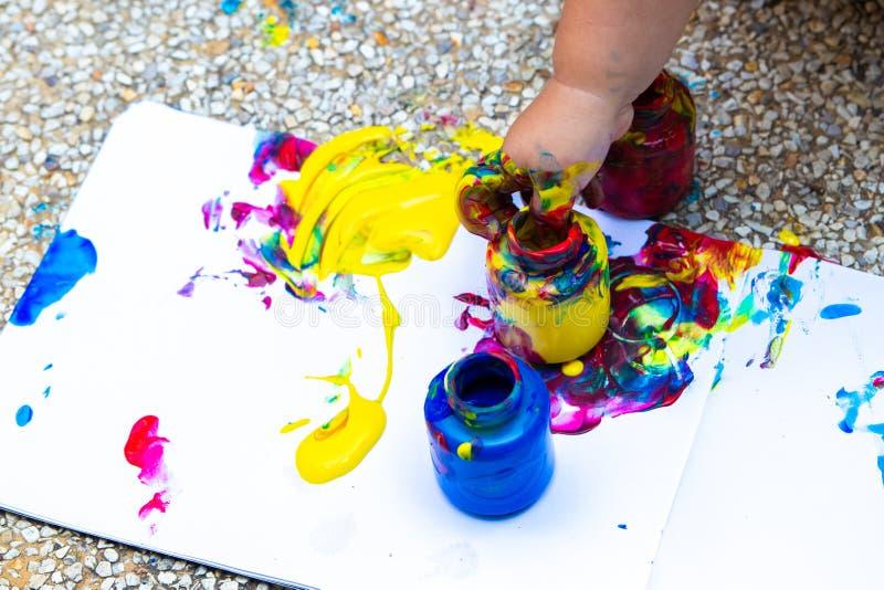 De kindhand trekt een blauw, rood en gele vingerverf - op een wit blad van document Creatieve kindontwikkeling binnen stock foto's