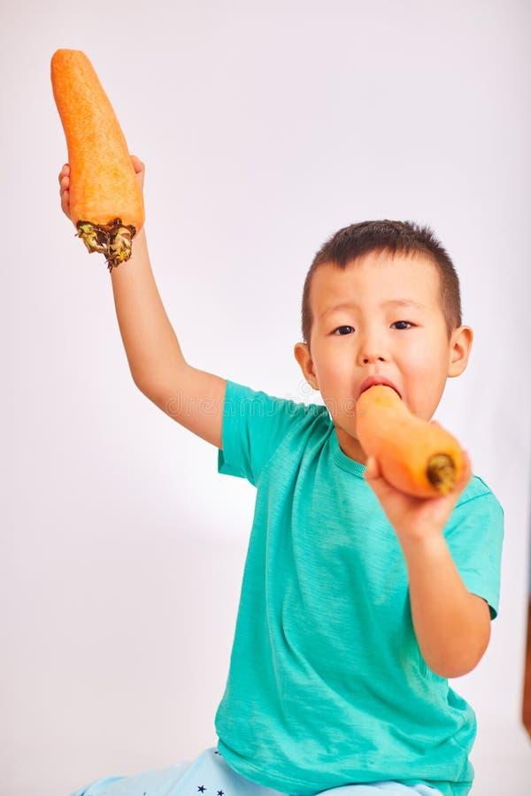 De kindjongen in een turkoois overhemd, die reusachtige wortelen eten, één wortel hief omhoog op - fruit en gezond voedsel royalty-vrije stock foto's