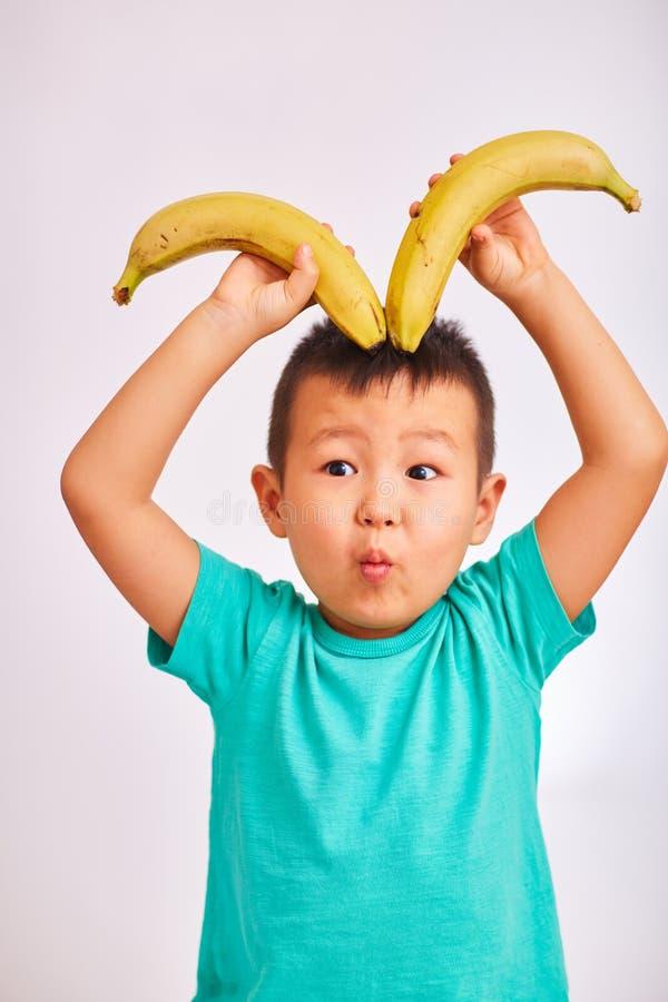 De kindjongen in een turkoois overhemd, houdt bananen afschilderend hoornen en kijkt met afgevlakte ogen - fruit en gezond voedse stock afbeeldingen