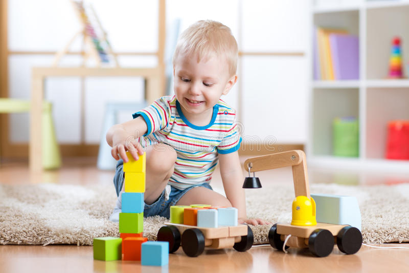 De kindjongen is gelukkig om stuk speelgoed bouwstenen en laderauto te spelen stock fotografie