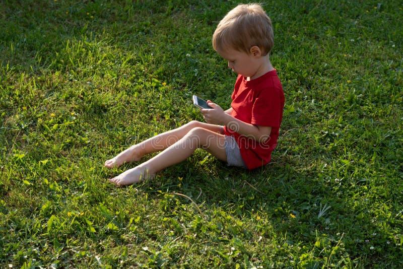 De kindjongen onderzoekt een mobiele telefoon terwijl het zitten op het gras Het concept onderwijs en afhankelijkheid van gadgets stock afbeelding