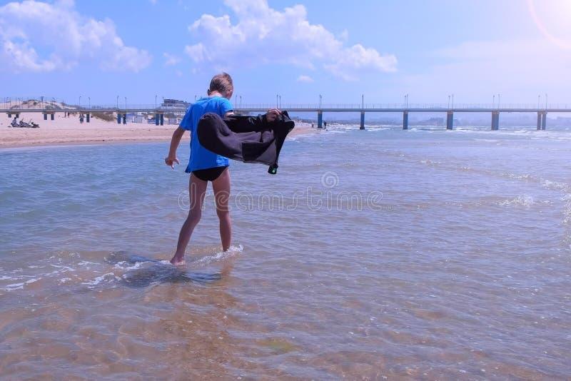 De kindjongen op overzeese vakantie loopt op zee waterrust op zandig strand in winderige dag royalty-vrije stock fotografie