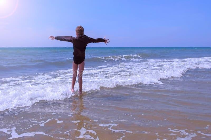 De kindjongen speelt en springt op zee onder golven in winderige zonnige dag op vakantie stock afbeelding