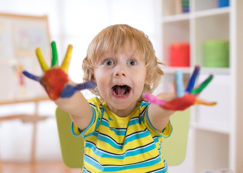 De kindjongen trekt met handen en toont multi-colored geschilderde palmen Kinderen` s onderwijsspelen met verven stock afbeeldingen