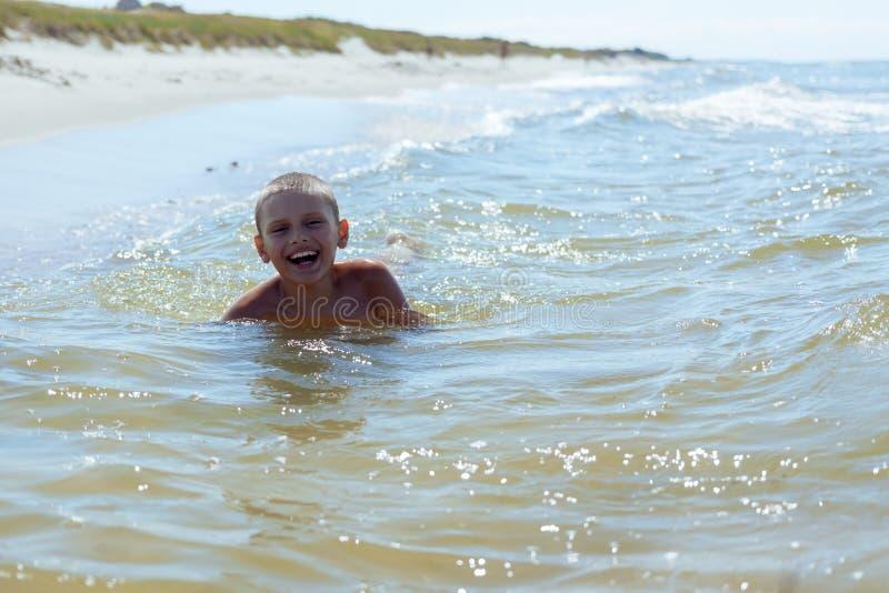 De kindjongen zwemt in overzees stock foto's