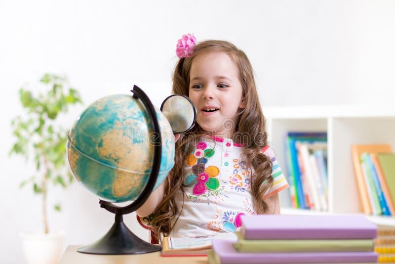 De kindlezing met vergrootglas kijkt de bol stock foto's