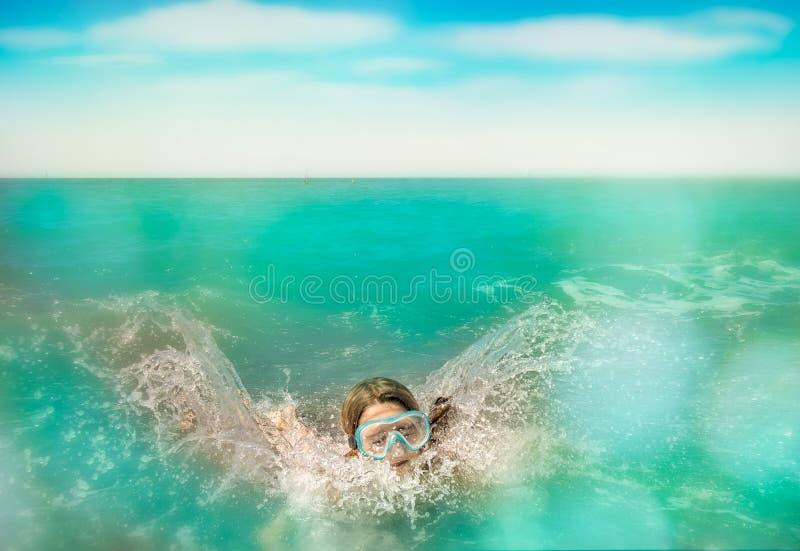 De kindonderdompeling en zwemt in het water stock foto