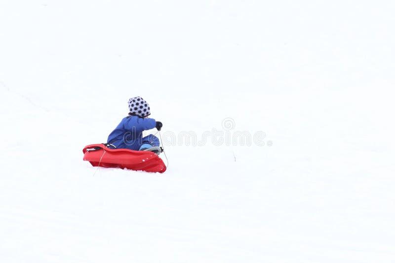 De kindritten in de winter op een slee op een sneeuwstraat Activiteit van het groeien van generatie in de verse lucht Gezond stock fotografie