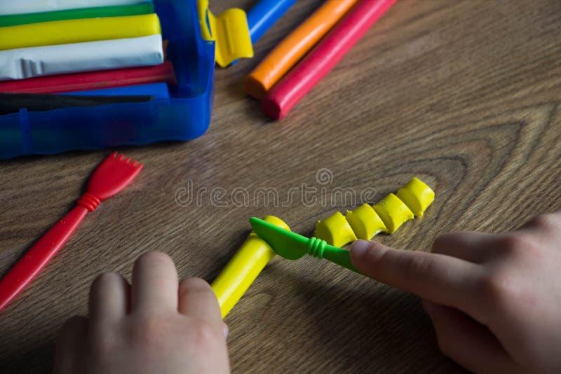 De kindspelen in een multi-colored plasticine op een houten lijst Creatief met kinderen royalty-vrije stock afbeelding