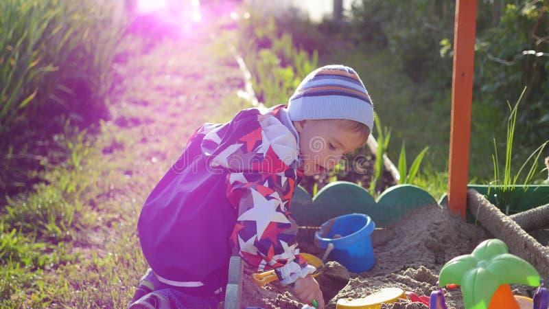 De kindspelen met het speelgoed in de zandbak De zonnige dag van de zomer Pret en spelen in openlucht royalty-vrije stock foto's