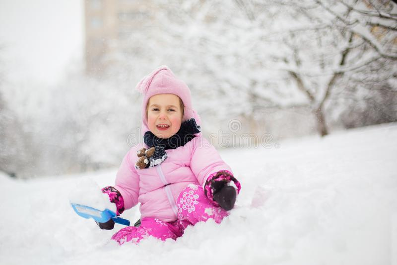 De kindspelen met sneeuw in de winter Een klein meisje in een helder jasje en gebreide hoed, vangstensneeuwvlokken in een de wint royalty-vrije stock fotografie