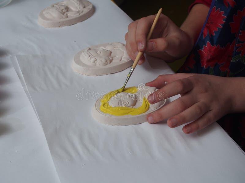De kindverven pleisteren bas-hulp met verven stock fotografie