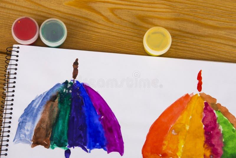 De kindverven in waterverf, het schilderen Kinderen` s tekening Het jonge geitje trekt een paraplu in alle kleuren van de regenbo royalty-vrije stock fotografie