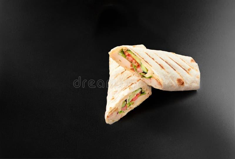 De kippenbroodje van het Shawarmavlees in een pitabroodje met verse groenten die op zwarte achtergrond voor de studio van het men stock foto