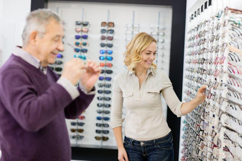 De klant kiest kaderglas met de hulp van de winkelarbeider royalty-vrije stock foto