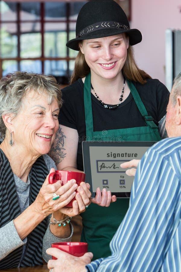 De klant ondertekent Tablet om op Koffiealgemene vergadering te betalen stock fotografie