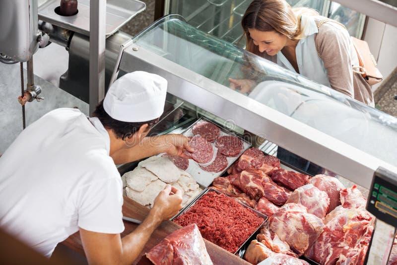 De Klant van slagersshowing meat to bij Slachterij royalty-vrije stock fotografie