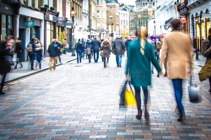 De klanten houden handen op de bezige hoofdstraat van Londen royalty-vrije stock fotografie