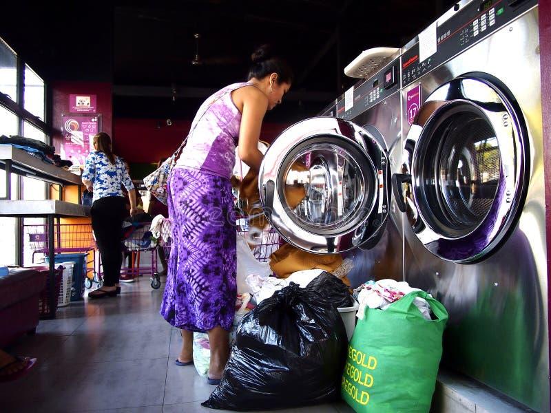 De klanten van laundromat vullen wasmachines en drogers met hun wasserij royalty-vrije stock afbeelding