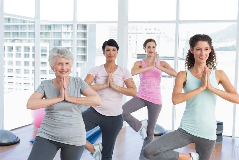 De klasse die zich in namaste bevinden stelt bij yogaklasse stock afbeelding