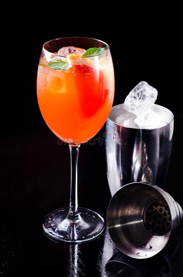 De klassieke Italiaanse cocktail van Aperol Spritz met oranje plak, verse munt, fruit in wijnglas en ijsblokje, schudbeker op bar stock foto's