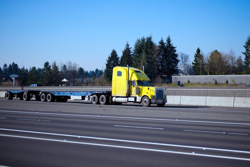 De klassieke semi aanhangwagen van het vrachtwagen gele vlakke bed op weg tusen staten stock fotografie