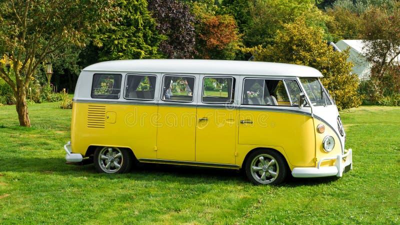 De klassieke uitstekende gele die Volkswagen-bestelwagen van de Vervoerderskampeerauto in het park, Devon, het UK, 26 Augustus, 2 royalty-vrije stock foto