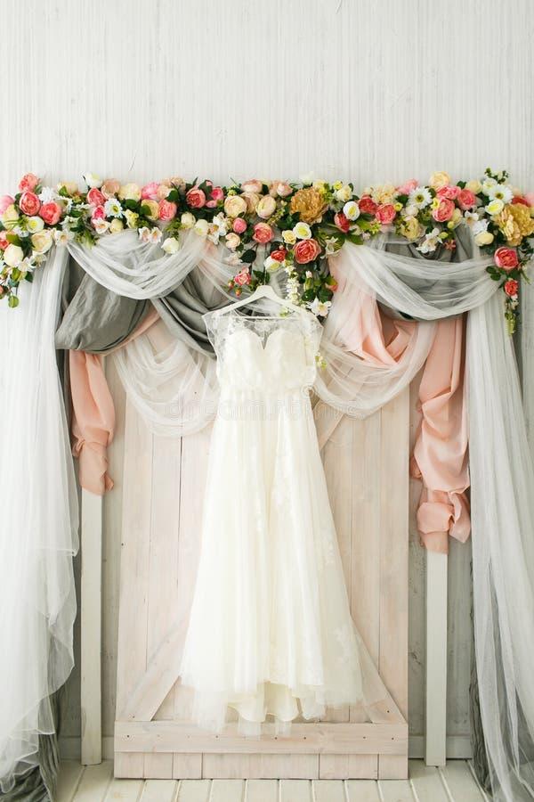 De kleding van de bruid hangt op een huwelijksboog stock foto's