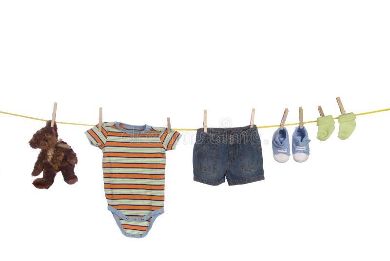 De kleding van de baby het hangen op drooglijn stock afbeelding