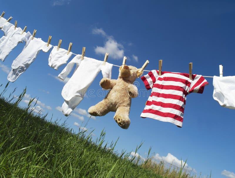 De kleding van de baby op een drooglijn stock fotografie