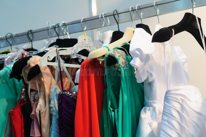 De kleding van de vrouw op hangers in opslag stock foto's