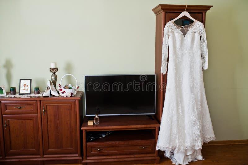 De kleding van het bruid` s huwelijk het hangen op de hanger in de ruimte stock foto