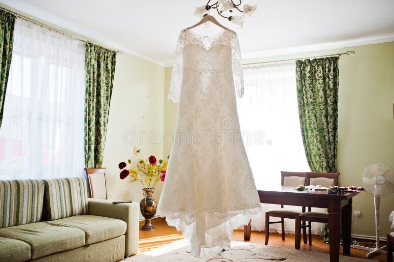 De kleding van het bruid` s huwelijk het hangen op de hanger in de ruimte stock afbeeldingen