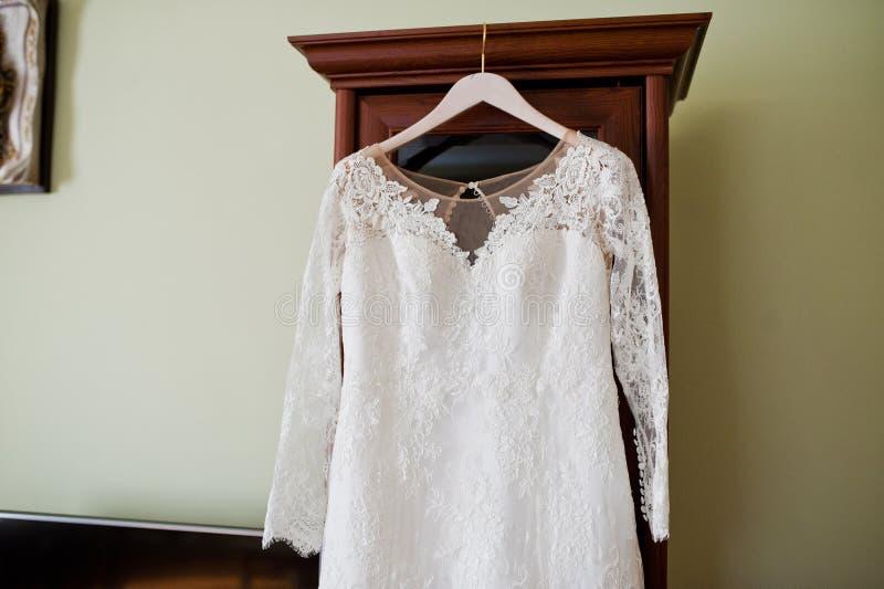De kleding van het bruid` s huwelijk het hangen op de hanger in de ruimte royalty-vrije stock afbeelding