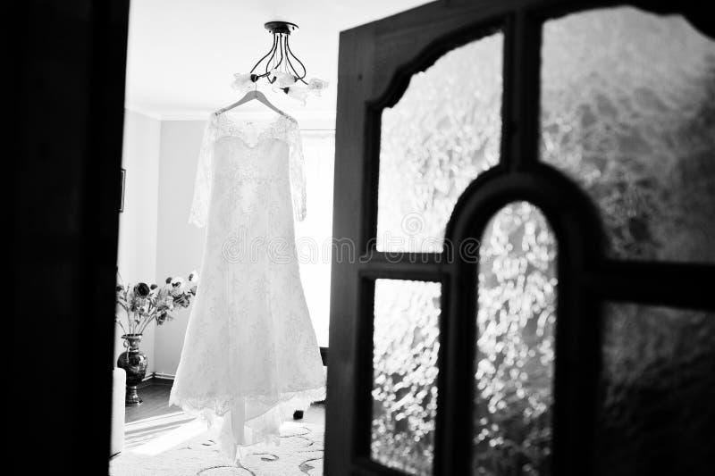 De kleding van het bruid` s huwelijk het hangen op de hanger in de ruimte Zwarte a royalty-vrije stock afbeelding