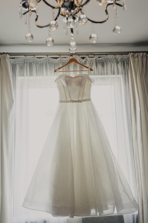 De kleding van het huwelijk Witte huwelijkskleding met een volledige rok op een hanger in de ruimte van de bruid met witte gordij stock afbeeldingen