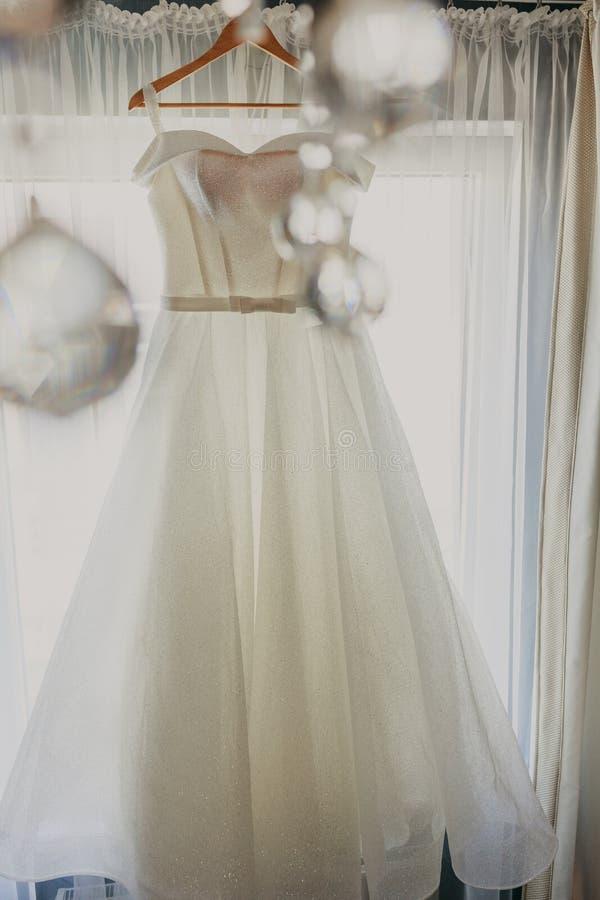 De kleding van het huwelijk Witte huwelijkskleding met een volledige rok op een hanger in de ruimte van de bruid met witte gordij royalty-vrije stock foto