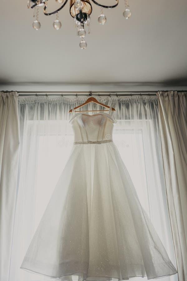 De kleding van het huwelijk Witte huwelijkskleding met een volledige rok op een hanger in de ruimte van de bruid met witte gordij stock afbeelding