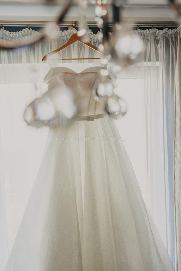 De kleding van het huwelijk Witte huwelijkskleding met een volledige rok op een hanger in de ruimte van de bruid met witte gordij royalty-vrije stock foto's