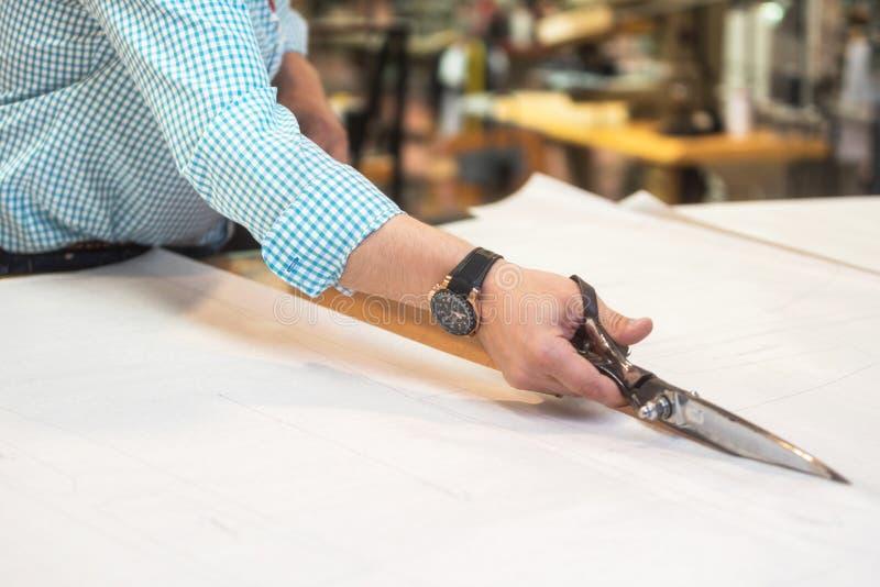 De kleermaker die het duidelijke patroon op stof met grote schaar op de werkbank in zijn winkel verwijderen, sluit omhoog mening  royalty-vrije stock fotografie