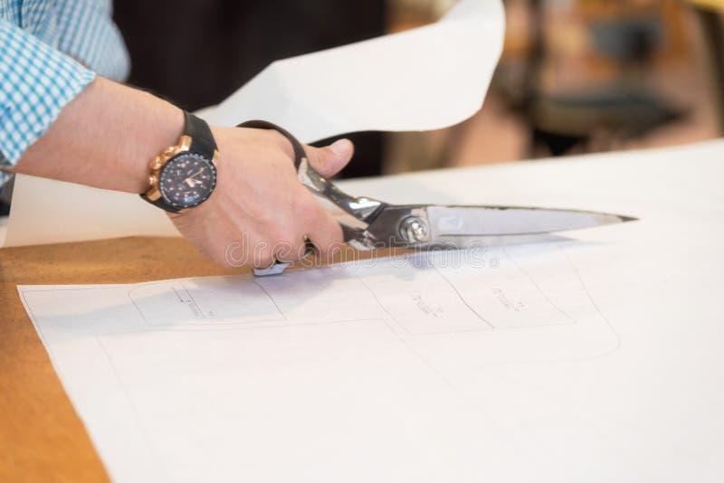 De kleermaker die het duidelijke patroon op stof met grote schaar op de werkbank in zijn winkel verwijderen, sluit omhoog mening  royalty-vrije stock foto's