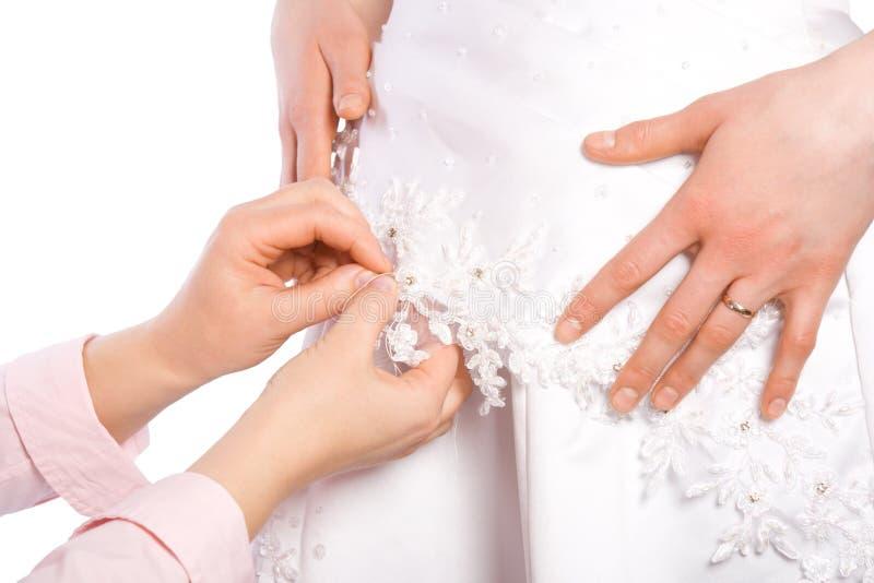 De kleermaker naait kleding van bruid stock fotografie