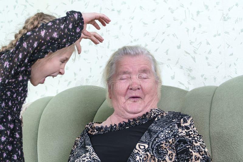 De kleindochter doet schrikken grootmoeder stock afbeelding