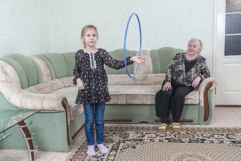 De kleindochter draait hoepel voor grootmoeder royalty-vrije stock fotografie