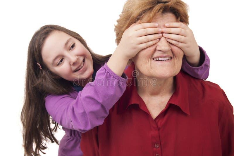 De kleindochter overhandigt dichte omhooggaand van grootmoederogen stock foto
