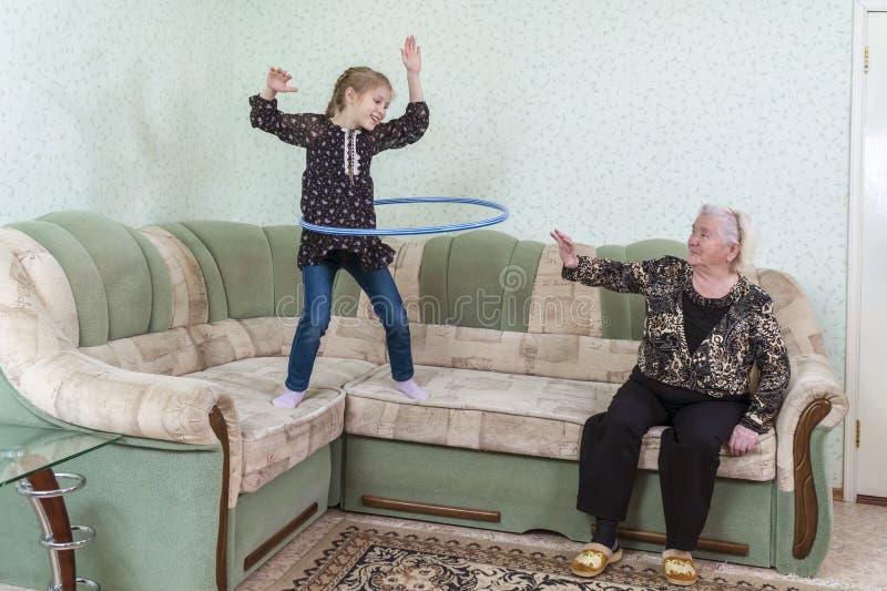 De kleindochter toont grootmoeder gymnastiek- oefeningen royalty-vrije stock afbeelding