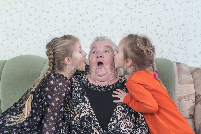 De kleindochters kussen hun groot-grootmoeder stock fotografie