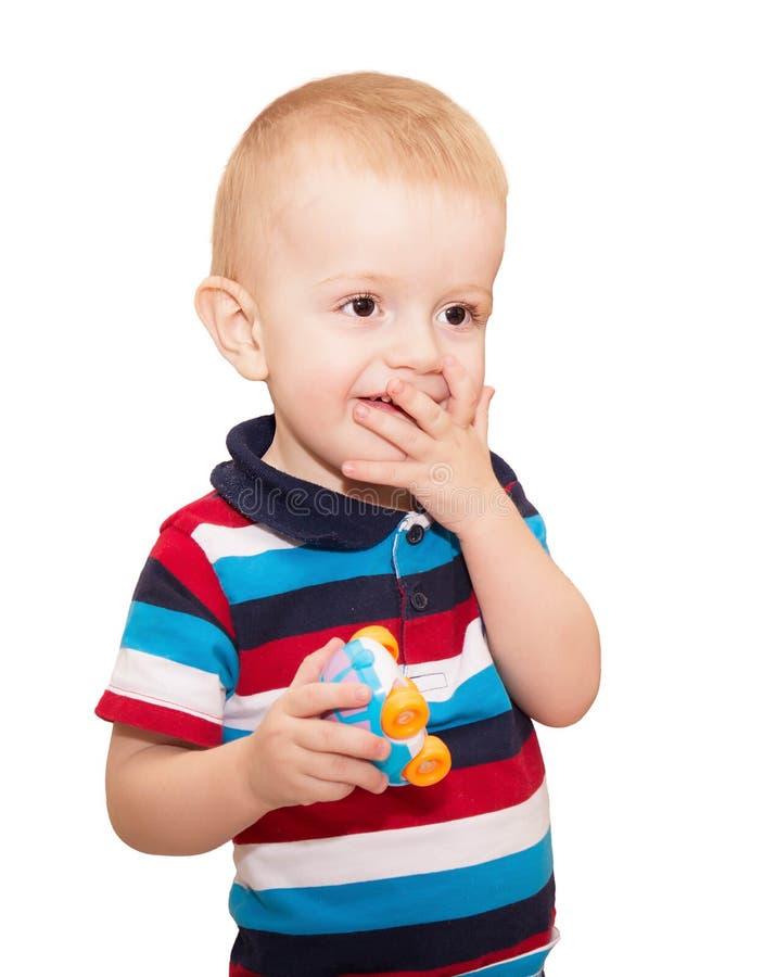 De kleine blonde jongen in een gestreepte t-shirt behandelde een mond royalty-vrije stock fotografie