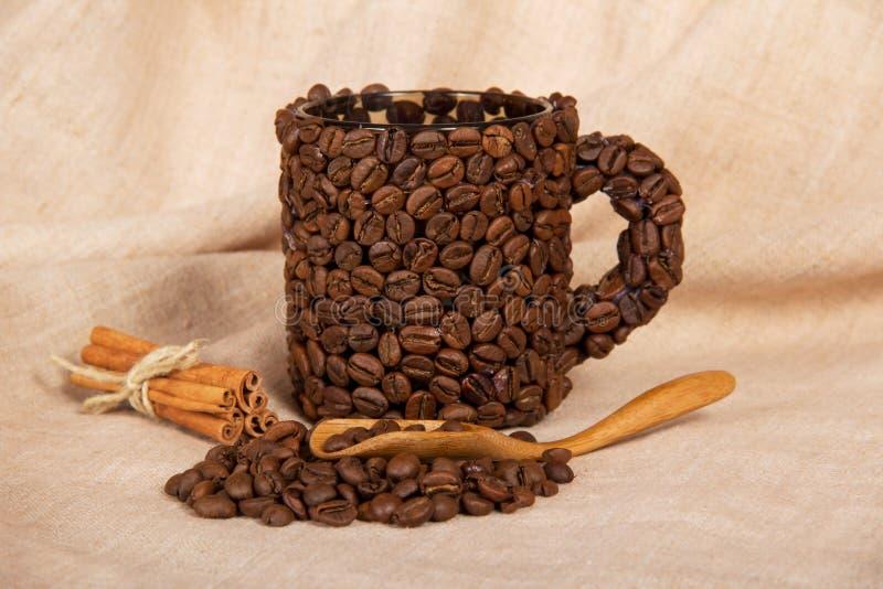 De kleine bonen van de stapelkoffie, kop, lepel, plakt kaneel op jute royalty-vrije stock foto