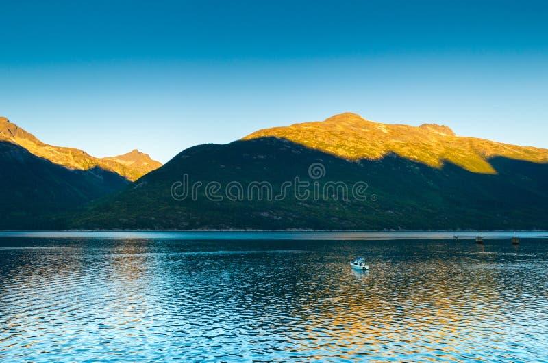 De kleine boot en de zonsopgang lon kalmeren vroege ochtend in Taiya-Inham, Skagway, Alaska royalty-vrije stock foto's